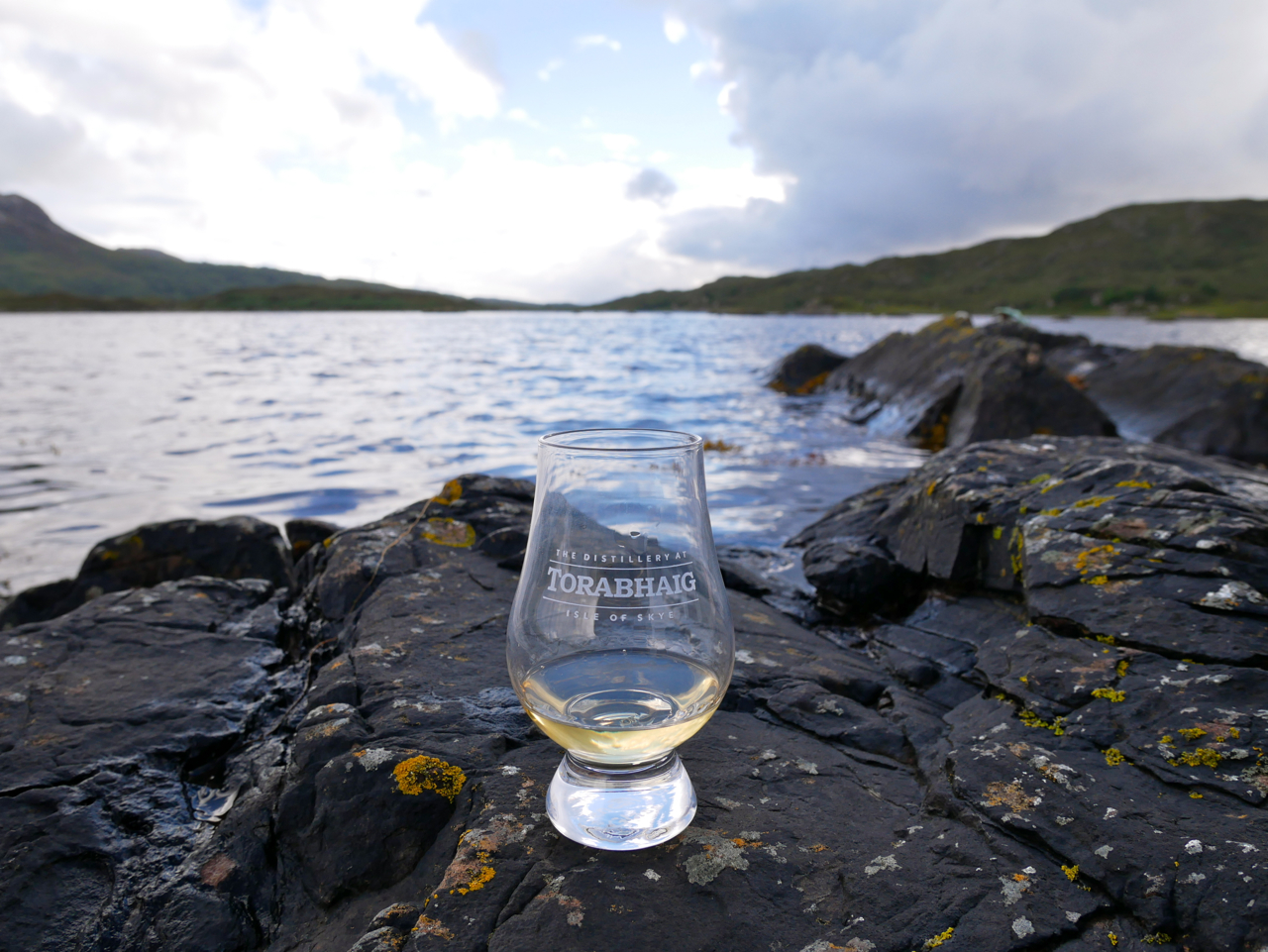 Blick auf schottische Küste auf der Isle of Skye bei Torabhaig Single Malt Scotch Whisky Destillerie mit Whisky in Glencairn Whiskyglas Nosingglas